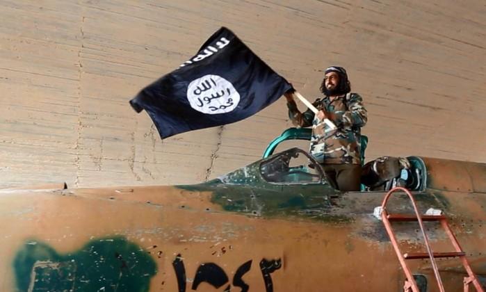 Militante do ISIS sobre um caça sírio capturado.
