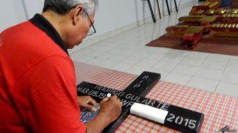 Funcionário do presídio prepara uma cruz com o nome de Rodrigo.
